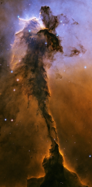 Appearing like a winged fairy-tale creature poised on a pedestal, this object is actually a billowing tower of cold gas and dust rising from a stellar nursery called the Eagle Nebula. The soaring tower is 9.5 light-years or about 90 trillion kilometres high, about twice the distance from our Sun to the next nearest star. Stars in the Eagle Nebula are born in clouds of cold hydrogen gas that reside in chaotic neighbourhoods, where energy from young stars sculpts fantasy-like landscapes in the gas. The tower may be a giant incubator for those newborn stars. A torrent of ultraviolet light from a band of massive, hot, young stars [off the top of the image] is eroding the pillar. The starlight also is responsible for illuminating the tower's rough surface. Ghostly streamers of gas can be seen boiling off this surface, creating the haze around the structure and highlighting its three-dimensional shape. The column is silhouetted against the background glow of more distant gas. The edge of the dark hydrogen cloud at the top of the tower is resisting erosion, in a manner similar to that of brush among a field of prairie grass that is being swept up by fire. The fire quickly burns the grass but slows down when it encounters the dense brush. In this celestial case, thick clouds of hydrogen gas and dust have survived longer than their surroundings in the face of a blast of ultraviolet light from the hot, young stars. Inside the gaseous tower, stars may be forming. Some of those stars may have been created by dense gas collapsing under gravity. Other stars may be forming due to pressure from gas that has been heated by the neighbouring hot stars. The first wave of stars may have started forming before the massive star cluster began venting its scorching light. The star birth may have begun when denser regions of cold gas within the tower started collapsing under their own weight to make stars. The bumps and fingers of material in the centre of the tower are examples of these ste