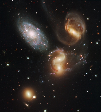 A clash among members of a famous galaxy quintet reveals an assortment of stars across a wide colour range, from young, blue stars to aging, red stars. This portrait of Stephan's Quintet, also known as the Hickson Compact Group 92, was taken by the new Wide Field Camera 3 (WFC3) aboard the NASA/ESA Hubble Space Telescope. Stephan's Quintet, as the name implies, is a group of five galaxies. The name, however, is a bit of a misnomer. Studies have shown that group member NGC 7320, at upper left, is actually a foreground galaxy that is about seven times closer to Earth than the rest of the group. Three of the galaxies have distorted shapes, elongated spiral arms, and long, gaseous tidal tails containing myriad star clusters, proof of their close encounters. These interactions have sparked a frenzy of star birth in the central pair of galaxies. This drama is being played out against a rich backdrop of faraway galaxies. The image, taken in visible and near-infrared light, showcases WFC3's broad wavelength range. The colours trace the ages of the stellar populations, showing that star birth occurred at different epochs, stretching over hundreds of millions of years. The camera's infrared vision also peers through curtains of dust to see groupings of stars that cannot be seen in visible light. NGC 7319, at top right, is a barred spiral with distinct spiral arms that follow nearly 180 degrees back to the bar. The blue specks in the spiral arm at the top of NGC 7319 and the red dots just above and to the right of the core are clusters of many thousands of stars. Most of the Quintet is too far away even for Hubble to resolve individual stars. Continuing clockwise, the next galaxy appears to have two cores, but it is actually two galaxies, NGC 7318A and NGC 7318B. Encircling the galaxies are young, bright blue star clusters and pinkish clouds of glowing hydrogen where infant stars are being born. These stars are less than 10 million years old and have not yet blown away their n