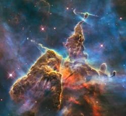 This craggy fantasy mountaintop enshrouded by wispy clouds looks like a bizarre landscape from Tolkien's The Lord of the Rings. The NASA/ESA Hubble Space Telescope image, which is even more dramatic than fiction, captures the chaotic activity atop a pillar of gas and dust, three light-years tall, which is being eaten away by the brilliant light from nearby bright stars. The pillar is also being assaulted from within, as infant stars buried inside it fire off jets of gas that can be seen streaming from towering peaks. This turbulent cosmic pinnacle lies within a tempestuous stellar nursery called the Carina Nebula, located 7500 light-years away in the southern constellation of Carina. The image celebrates the 20th anniversary of Hubble's launch and deployment into an orbit around the Earth. Scorching radiation and fast winds (streams of charged particles) from super-hot newborn stars in the nebula are shaping and compressing the pillar, causing new stars to form within it. Streamers of hot ionised gas can be seen flowing off the ridges of the structure, and wispy veils of gas and dust, illuminated by starlight, float around its towering peaks. The denser parts of the pillar are resisting being eroded by radiation. Nestled inside this dense mountain are fledgling stars. Long streamers of gas can be seen shooting in opposite directions from the pedestal at the top of the image. Another pair of jets is visible at another peak near the centre of the image. These jets, (known as HH 901 and HH 902, respectively, are signposts for new star birth and are launched by swirling gas and dust discs around the young stars, which allow material to slowly accrete onto the stellar surfaces. Hubble's Wide Field Camera 3 observed the pillar on 1-2 February 2010. The colours in this composite image correspond to the glow of oxygen (blue), hydrogen and nitrogen (green), and sulphur (red).