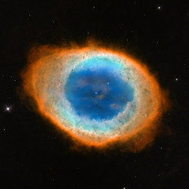 """This new image shows the dramatic shape and colour of the Ring Nebula, otherwise known as Messier 57. From Earth's perspective, the nebula looks like a simple elliptical shape with a shaggy boundary. However, new observations combining existing ground-based data with new NASA/ESA Hubble Space Telescope data show that the nebula is shaped like a distorted doughnut. This doughnut has a rugby-ball-shaped region of lower-density material slotted into in its central """"gap"""", stretching towards and away from us."""