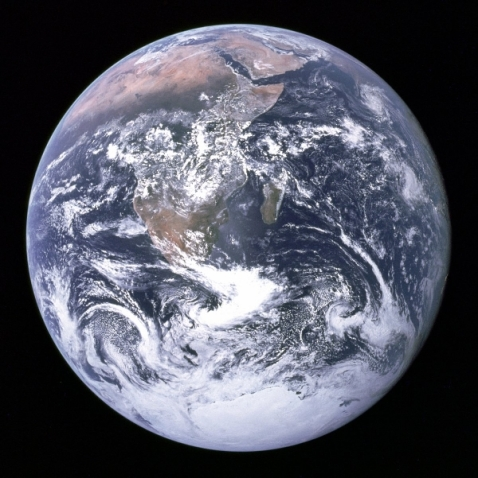 our-planet-appears-as-a-brilliant-blue-marble-wrapped-in-a-thin-nearly-invisible-veil-of-gas